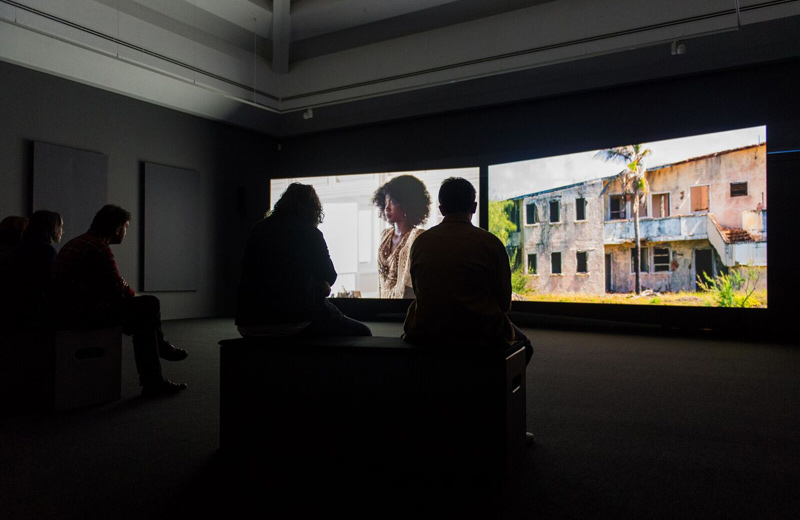 © John Akomfrah, Auto Da Fé, 2016. Two channel HD colour video installation, 5.1 sound 40 minutes 30 seconds. Artes Mundi 7 installation view, National Museum Cardiff, 2016. ©Smoking Dogs Films. Courtesy the artist and Lisson Gallery, London. Photos Polly Thomas.