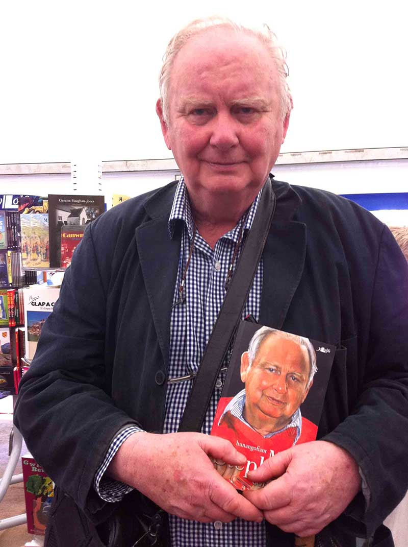 Photograph of Meic Stephens taken during the 2012 Eisteddfod. Meic is holding a copy of his Cofnodion, published by Y Lolfa. Image © Y Lolfa